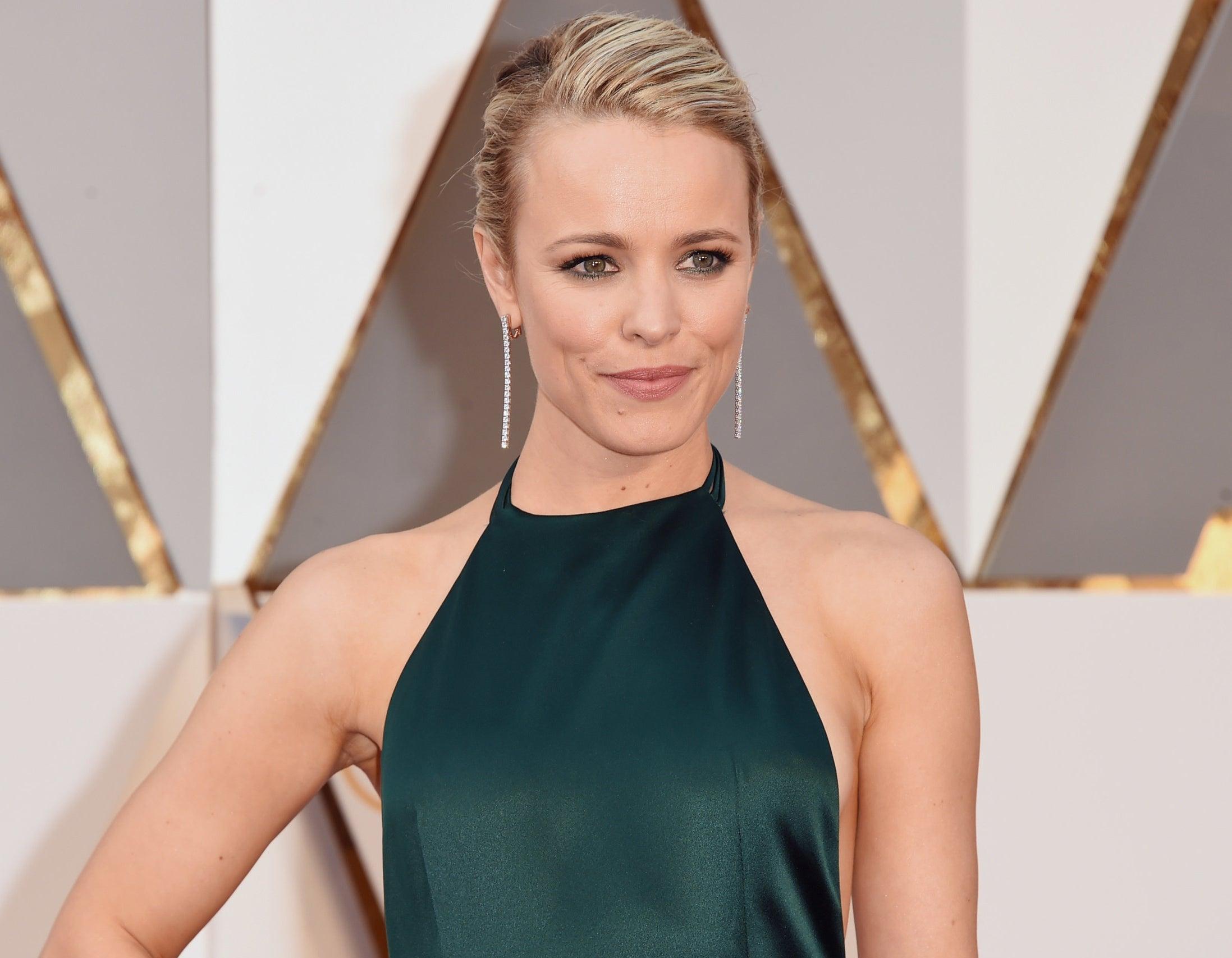 Rachel wears an emerald green halter dress to an event