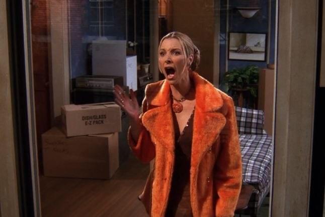 Phoebe, wearing an orange fuzzy long jacket, is mid scream.