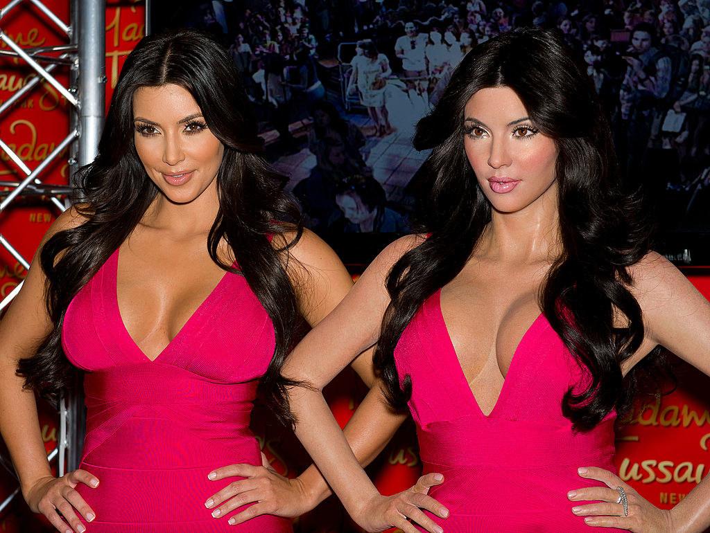 Kim Kardashian standing next to her wax figure wearing the same pink dress as it