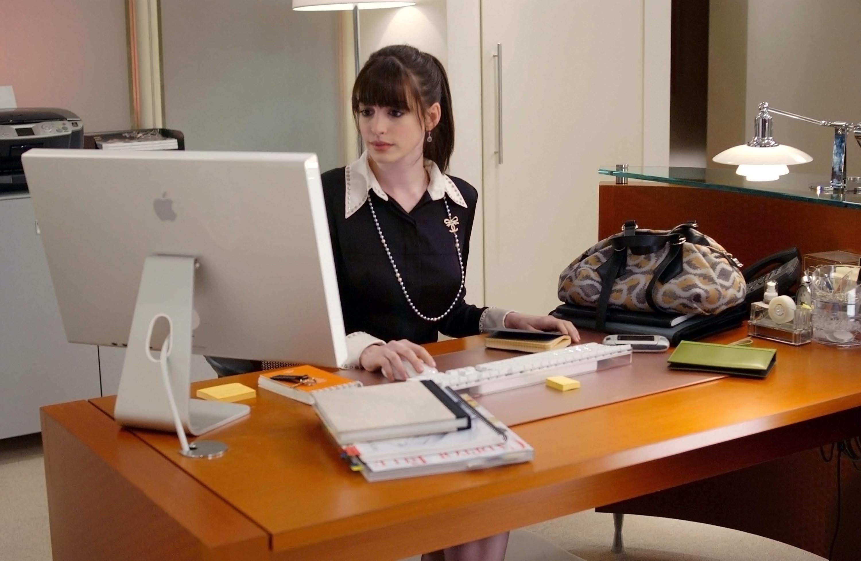 Anne sits at a desk in a scene from Devil Wears Prada