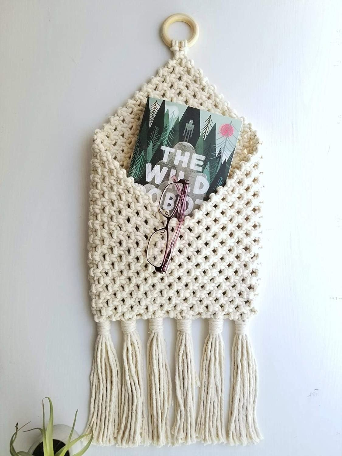 A macrame pouch hung on a wall with a pair of glasses and a magazine stored in it.