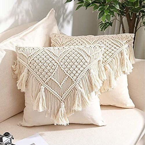 A pair of macrame cushions placed on a sofa.