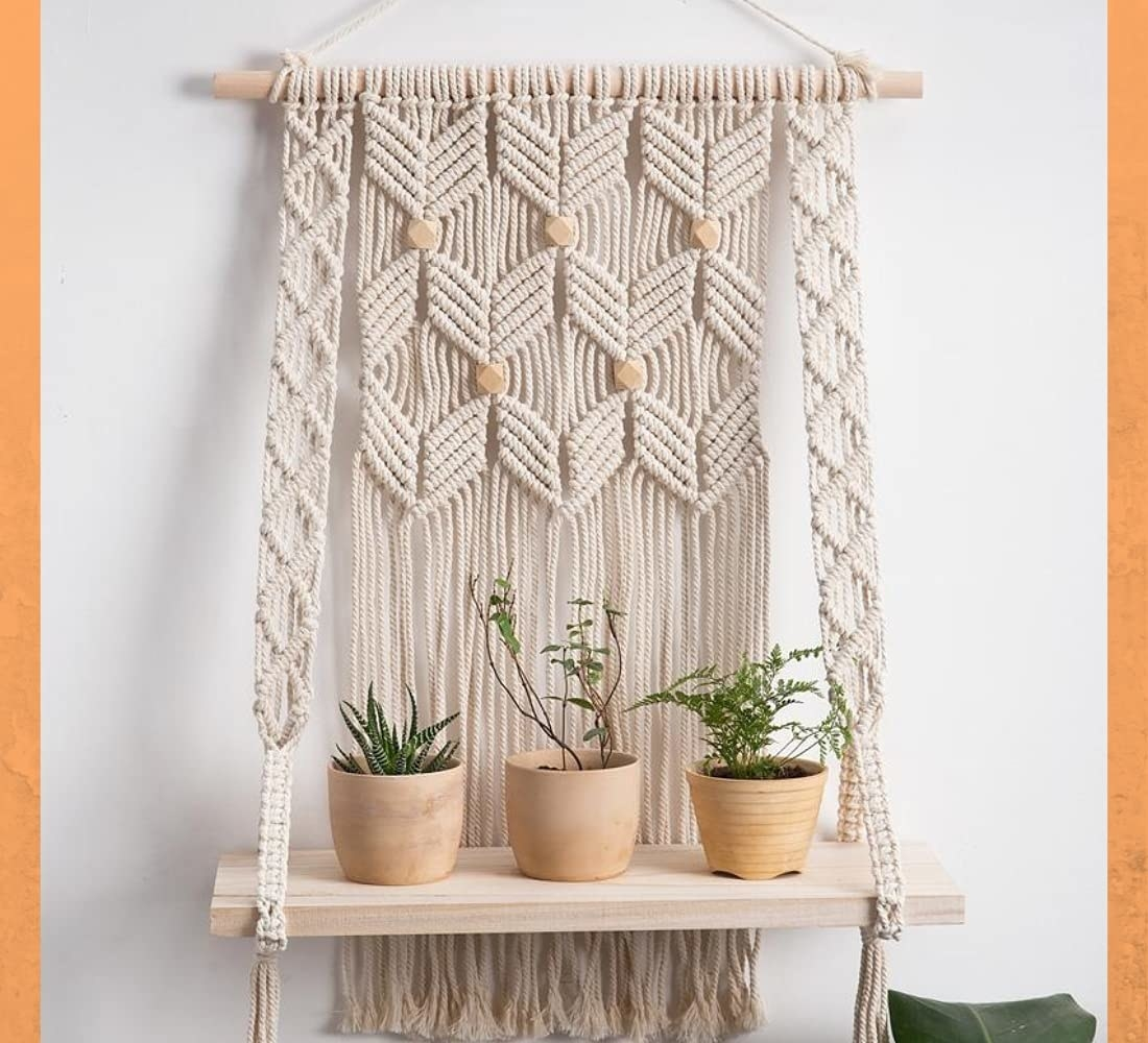 A macrame wall hanging with wooden shelf, holding 3 plants on it.