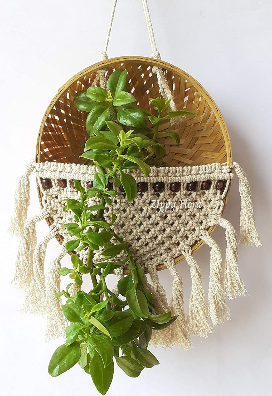 A macrame and bamboo hanging basket with a plant placed within it.