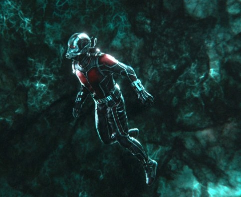 Ant-Man, in a miniature size, looks around at the green tinted world of the Quantum Realm.