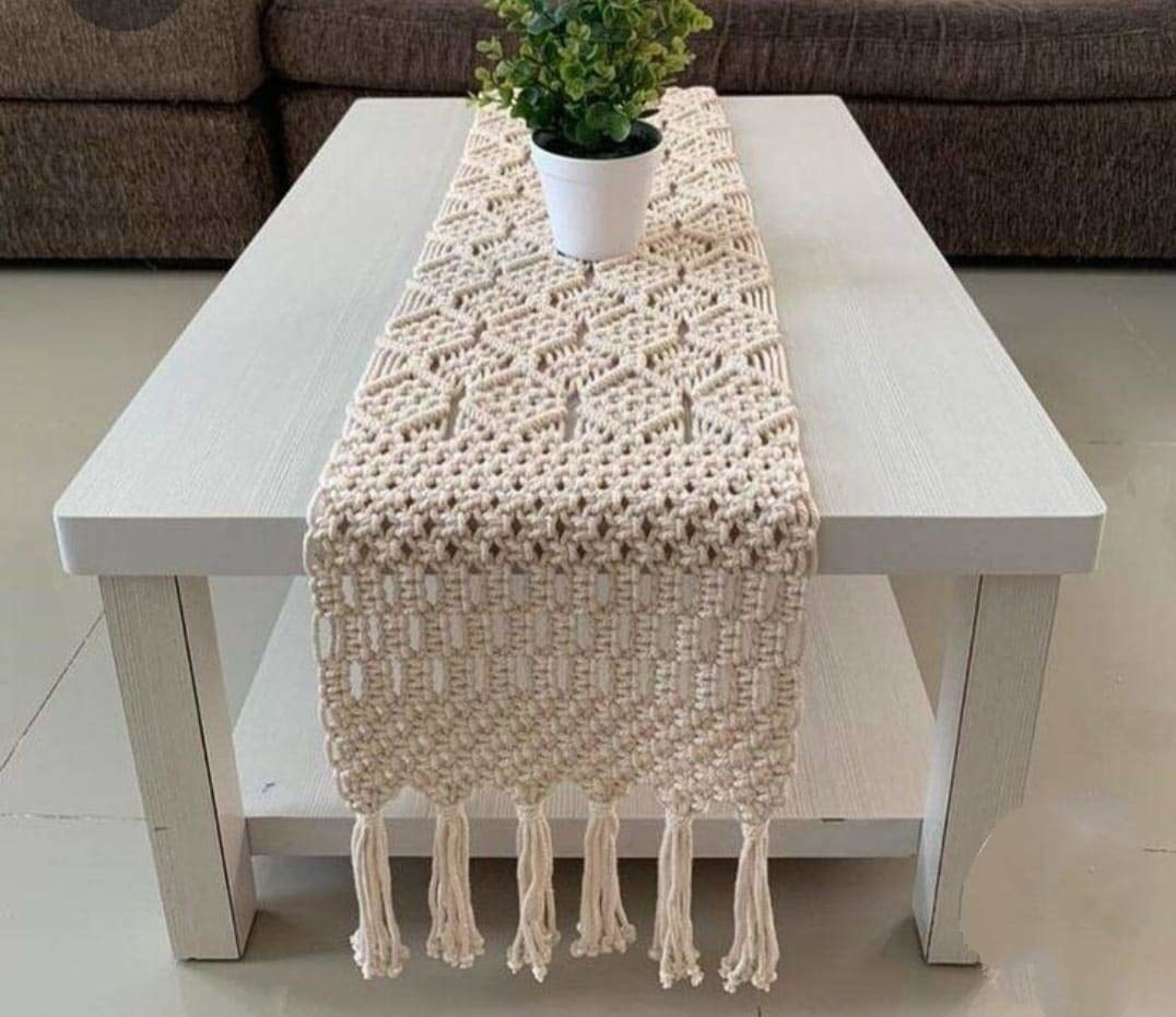 A beige macrame table runner placed on a white table.