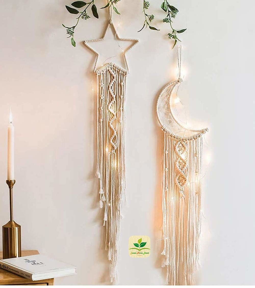 A pair of moon & star macrame dreamcatchers hanging on a wall.