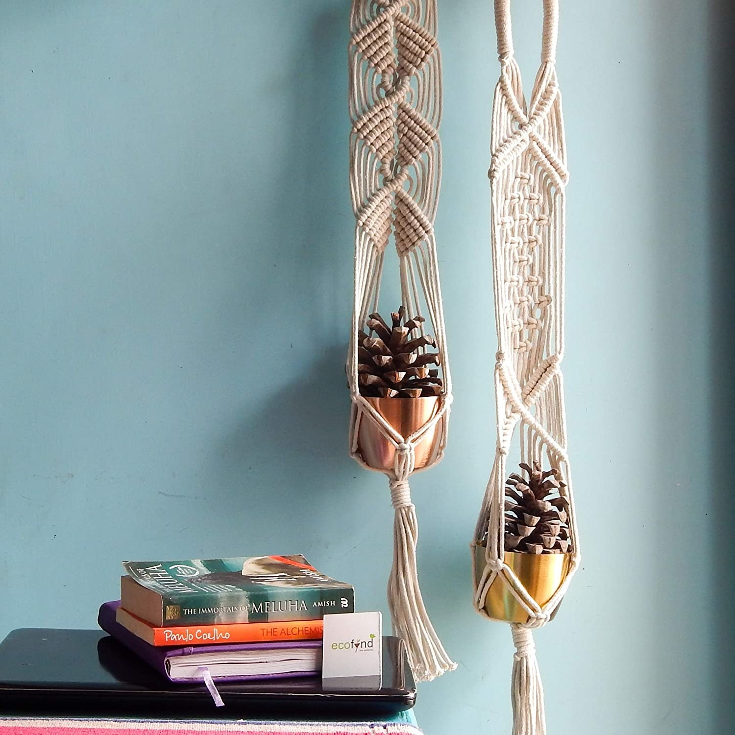 A pair of macrame plant hangers with metal pots placed in them.