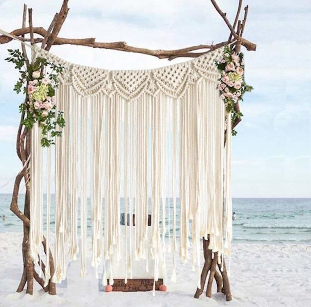 A macrame tapestry on a beach supported by wooden logs.