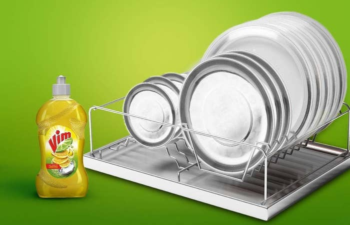 A bottle of Vim dishwashing liquid next to some clean plates on a dish rack.