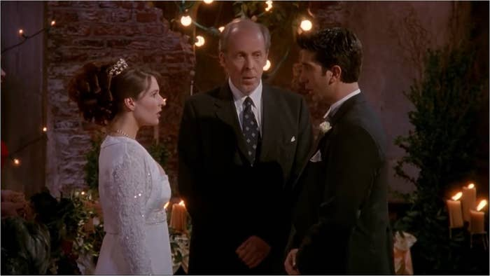 Ross and Emily stand together in front of a preacher on their wedding day.