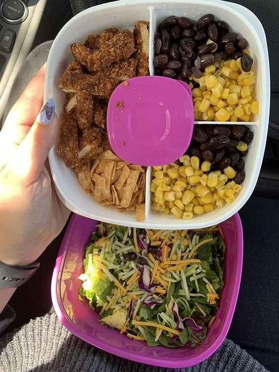 bento box style lunch container in green, holding salad in the bottom and veggies and dressing on the top divided portion