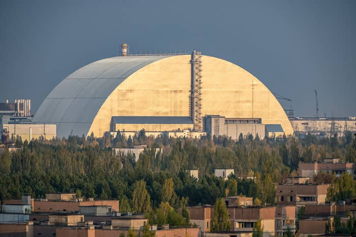 A large dome-like structure looming large in a semi-industrial and semi-residential landscape
