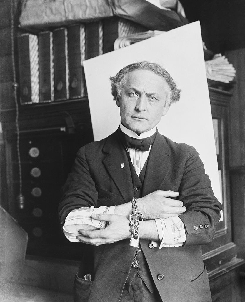 An older looking Harry Houdini posing with chains on his wrists