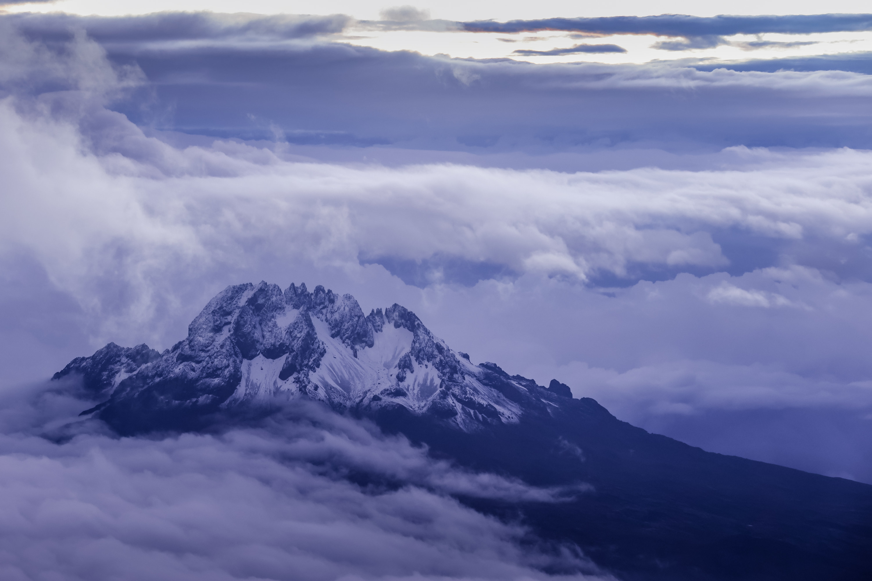 View of snow-capped Mount Kiliminjaro with white clouds surrounding the peak.
