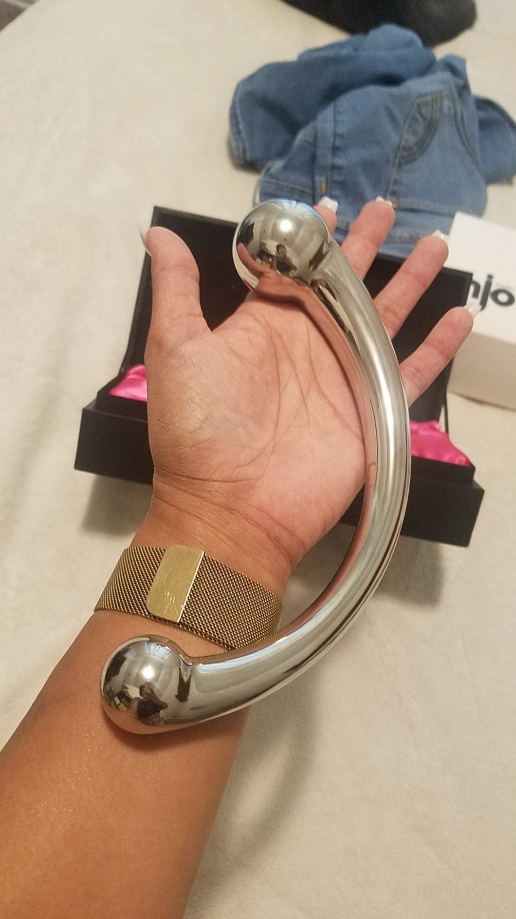 Model holding stainless steel dildo along palm and forearm