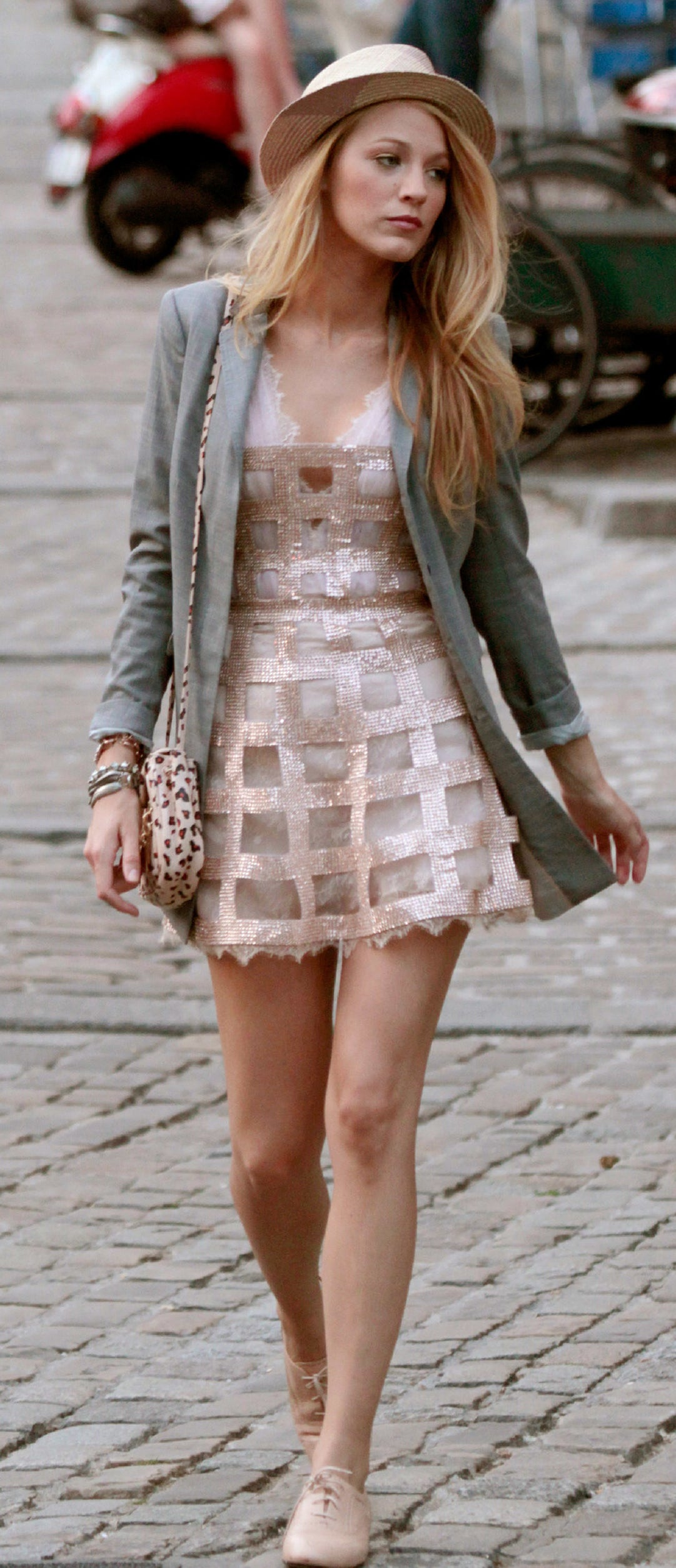 Serena in a short flare dress with lacy chiffon underneath and a v neck, and a sparkly grid overlay, with a leopard print purse, nude lace up booties, and a long blazer