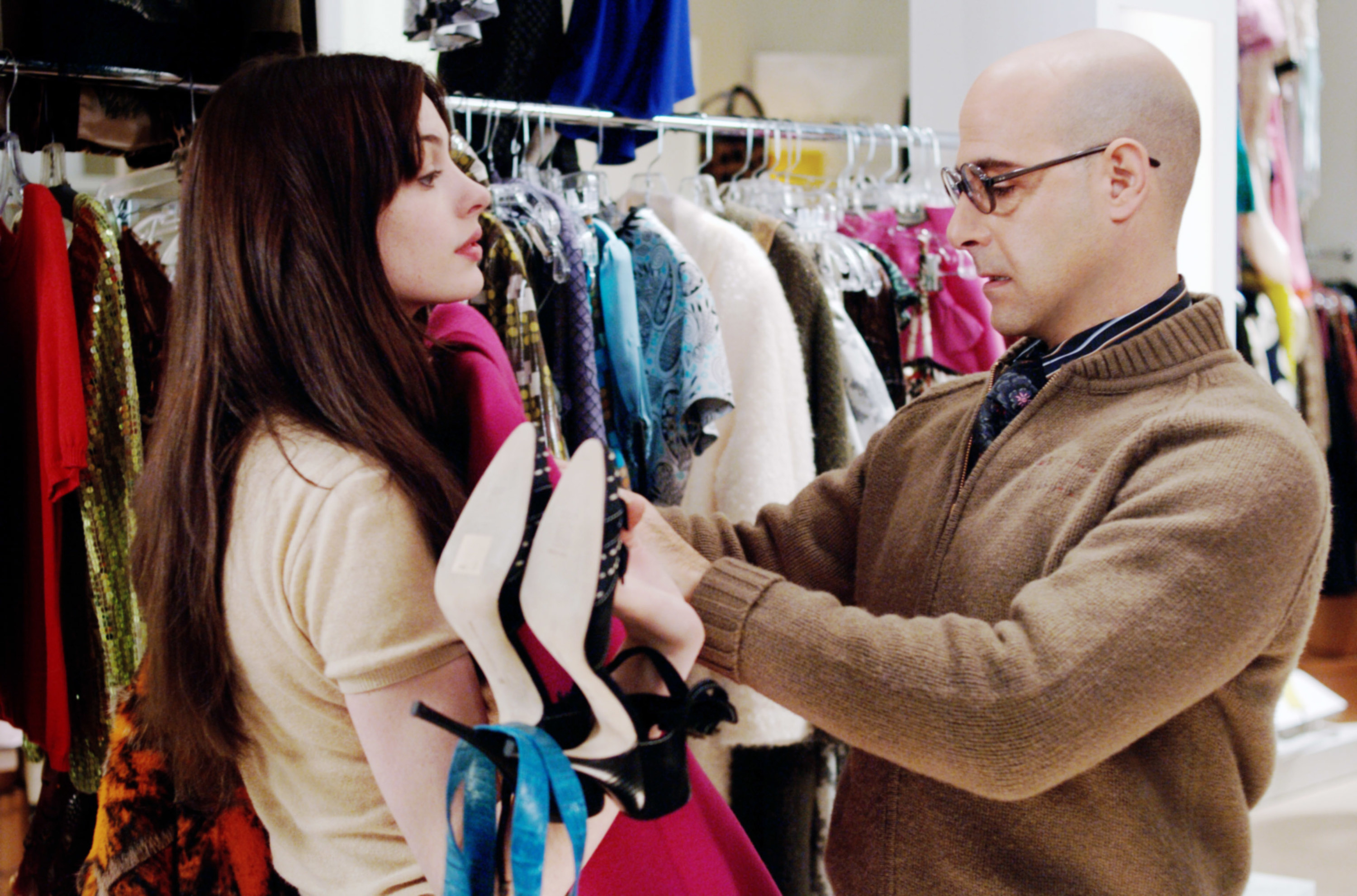 """Anne Hathaway and Stanley Tucci hold designer clothing on set of """"The Devil Wears Prada"""""""