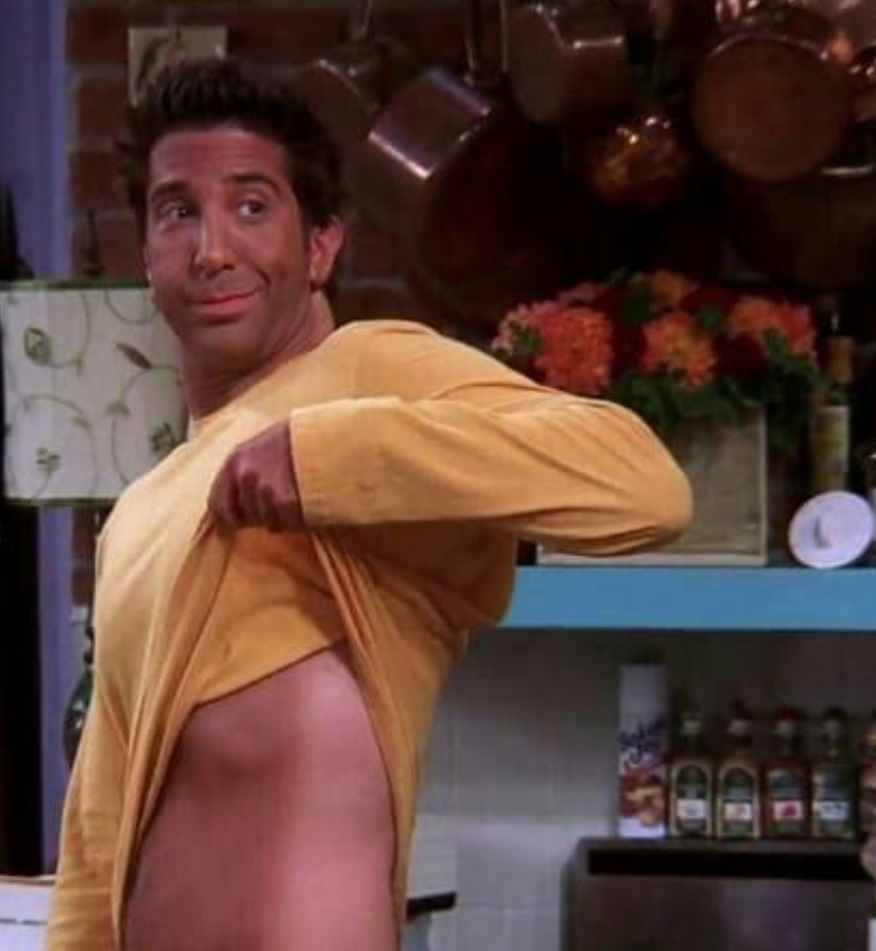 Ross holds up his shirt to show his darkly tanned front torso and face while his back is starkly white.