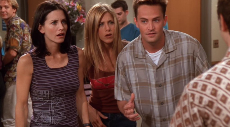 Rachel, Monica, and Chandler stand together with their mouths open in shock.