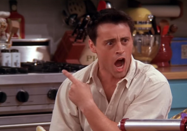 Joey sits at the kitchen table while pointing an index finger behind him and his mouth open in shock.