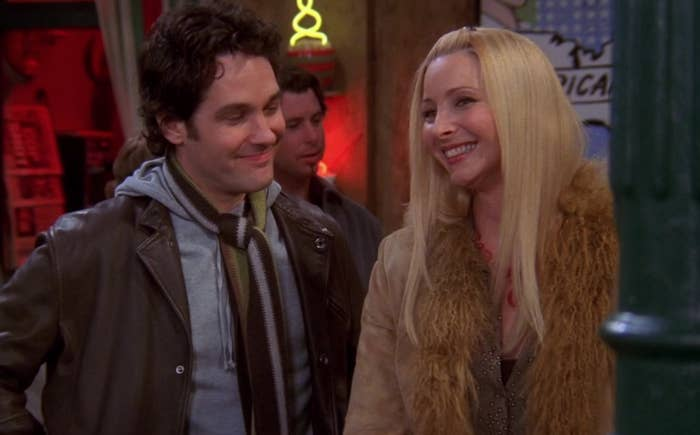 Mike smiles at Phoebe who grins at someone off screen at the Central Perk coffee shop.