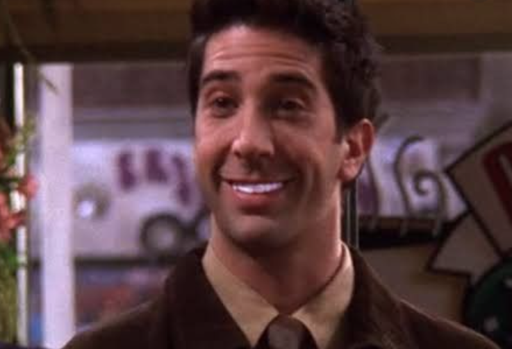 A close up shot of Ross who is showing off his blindly white teeth.