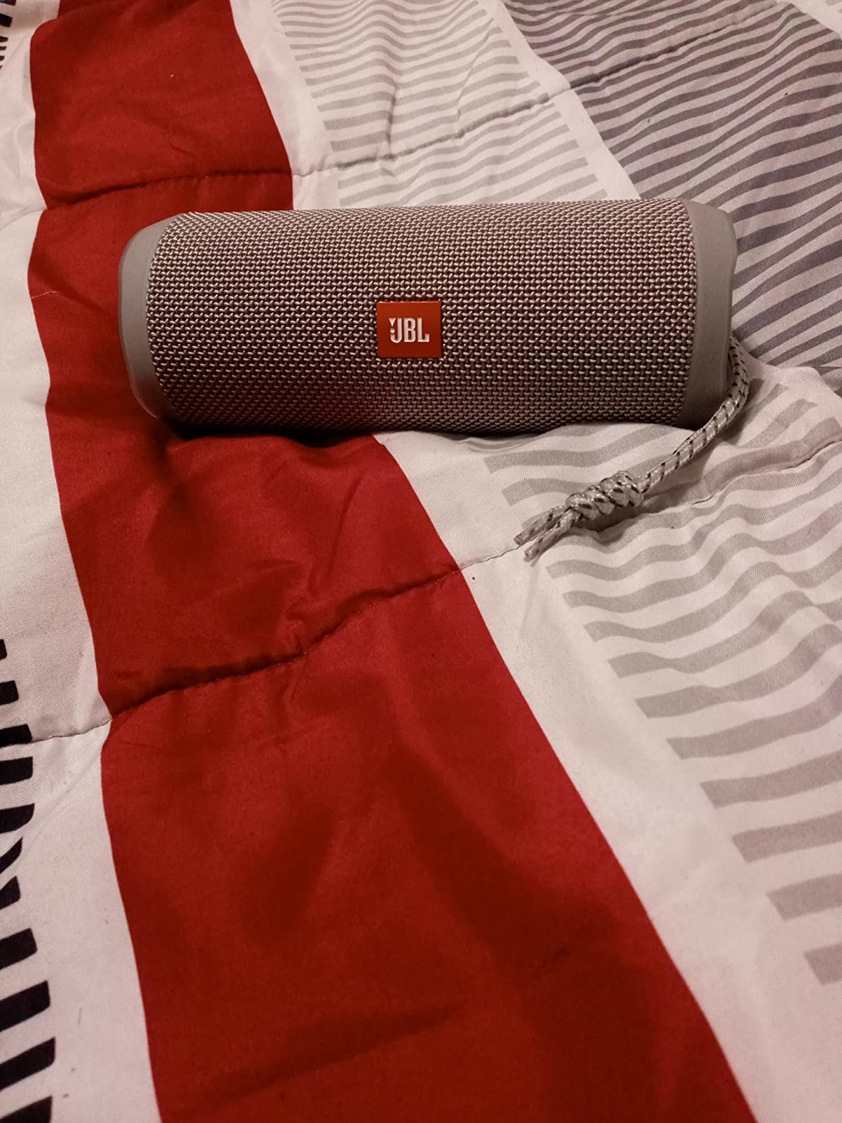 reviewer photo of the JBL speaker in gray on a bedspread