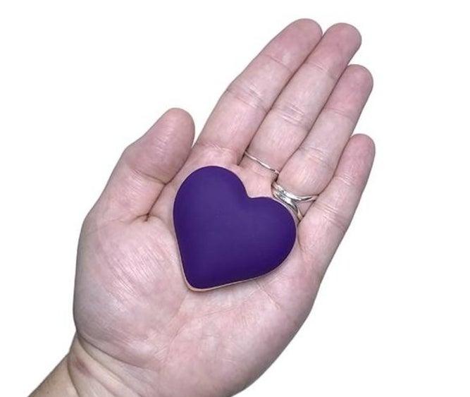 Model holding purple heart-shaped vibrator in palm
