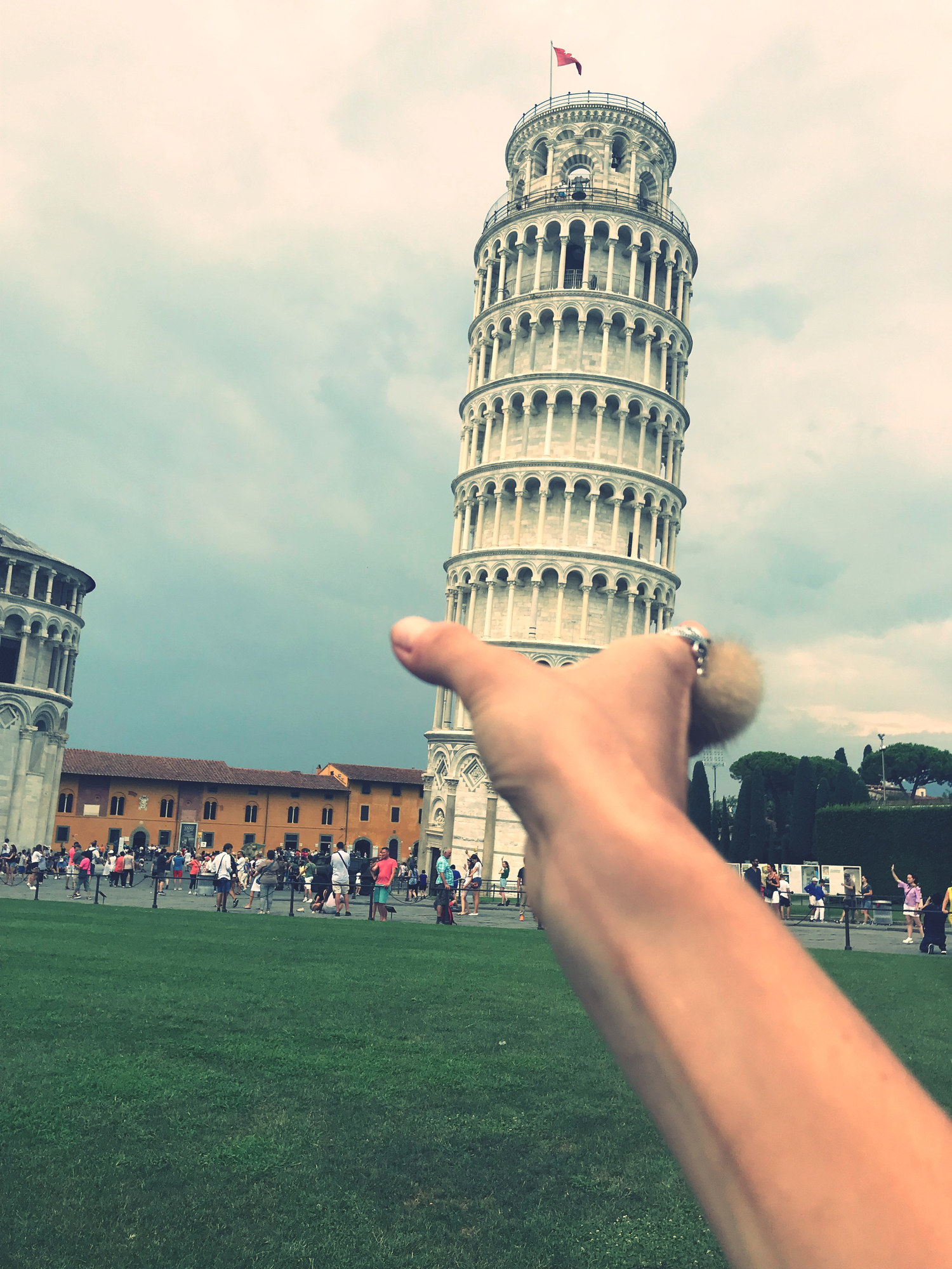 A hand pretending to hold the Leaning Tower of Pisa