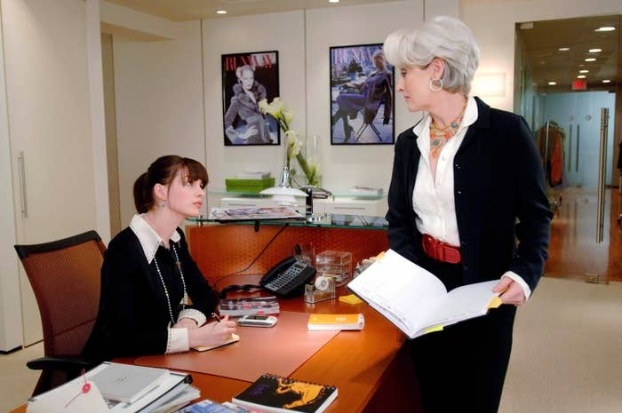 """Anne Hathaway and Meryl Streep talk to one another in an office on set of """"The Devil Wears Prada"""""""