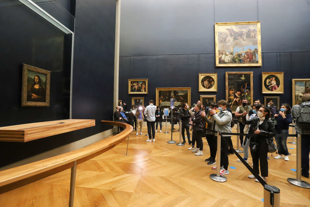 People gathering at the Louvre Museum in front of the Mona Lisa