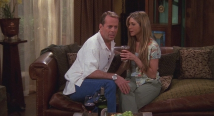 Paul and Rachel sits on the couch with his hand on her knee and her holding a drink.