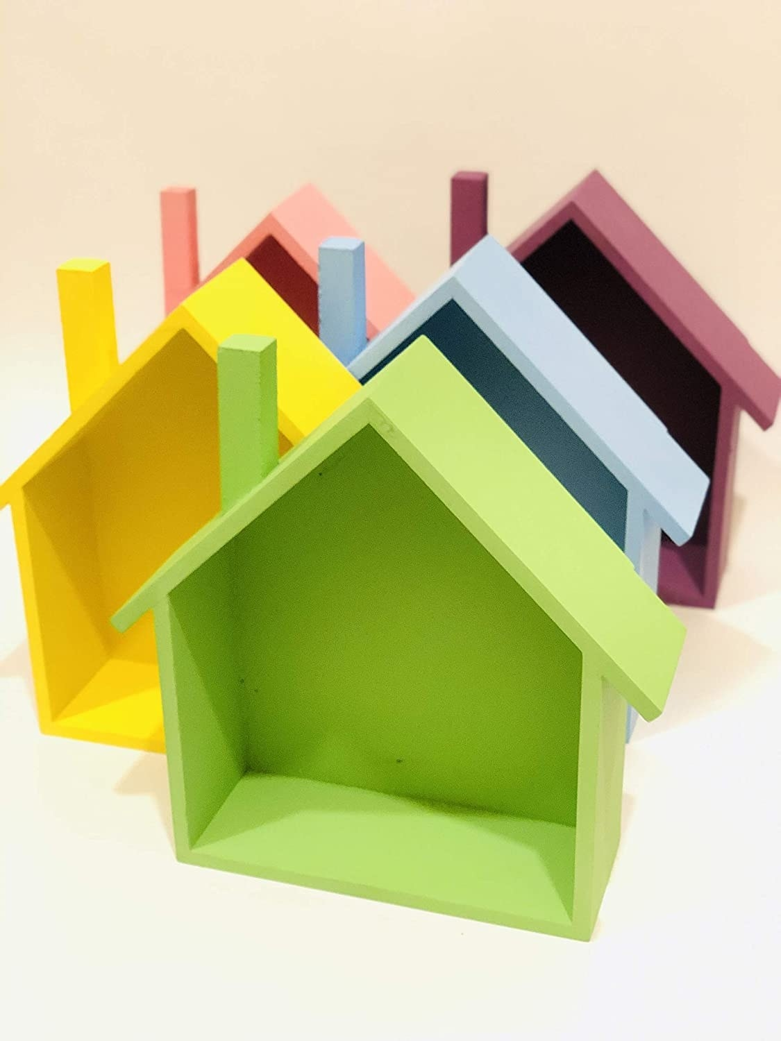 Five shelves shaped like homes in green, yellow, blue, pink and mauve.