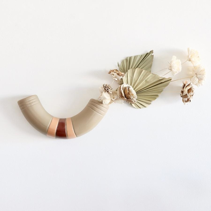 the wall vase that looks like a macaroni noodle with flowers inside