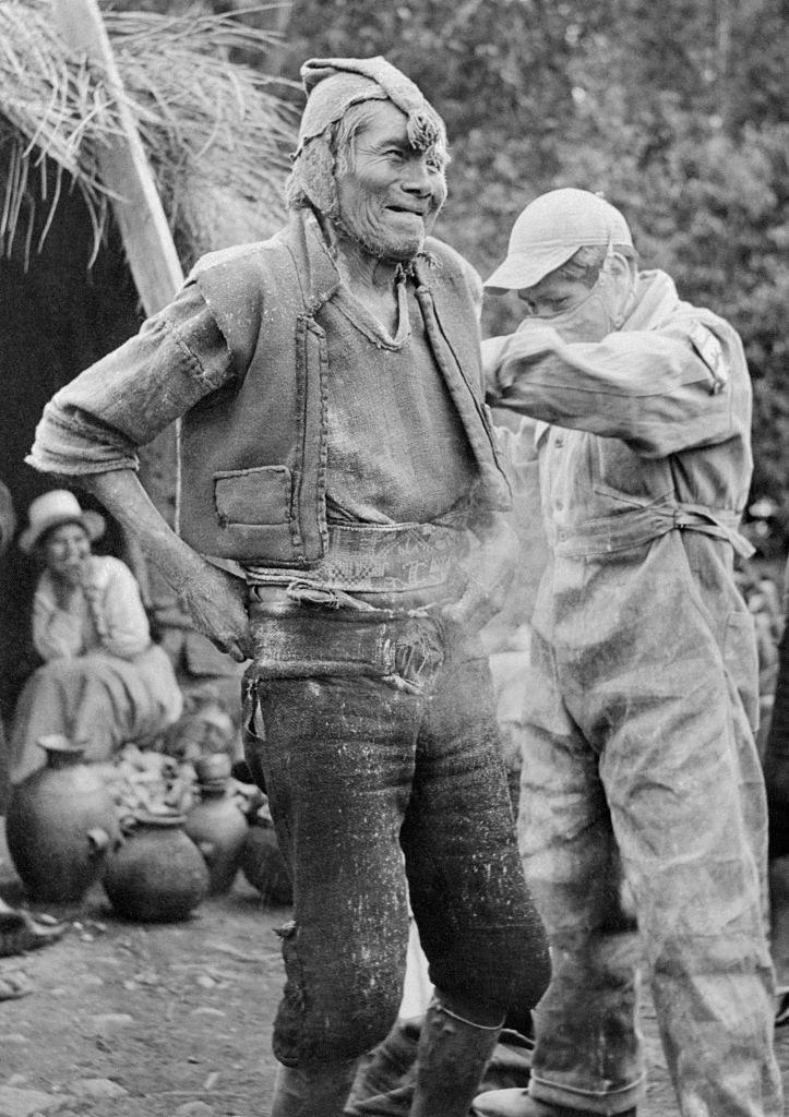 man spraying another man