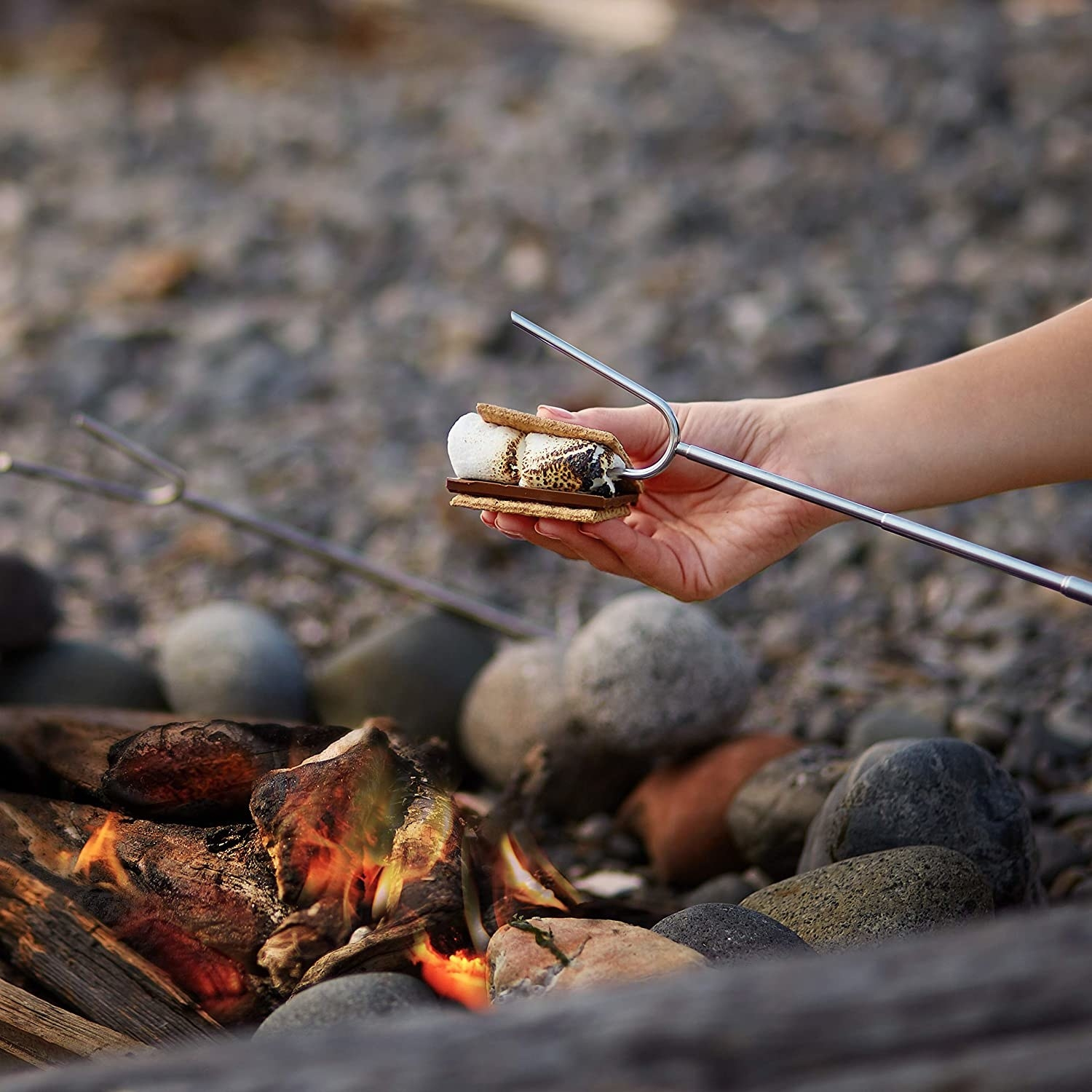 person putting marshmallows from the skewer into a smore