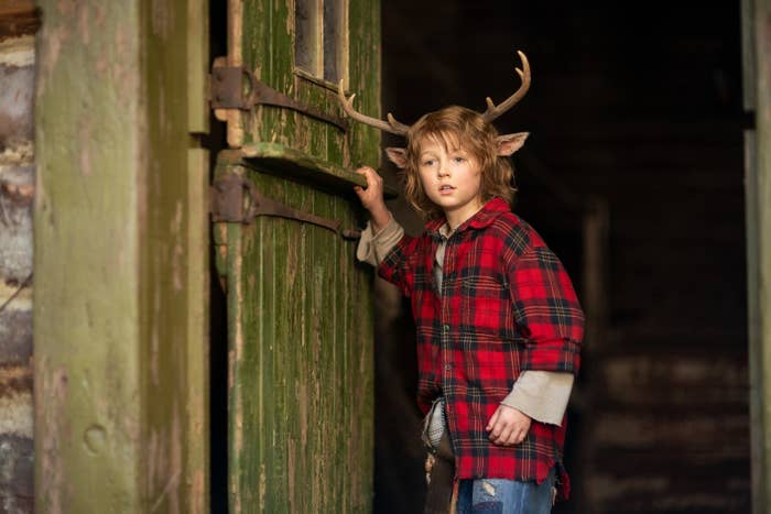 Actor Christian Convery, wearing deer antlers and a red flannel shirt, stands by an open door