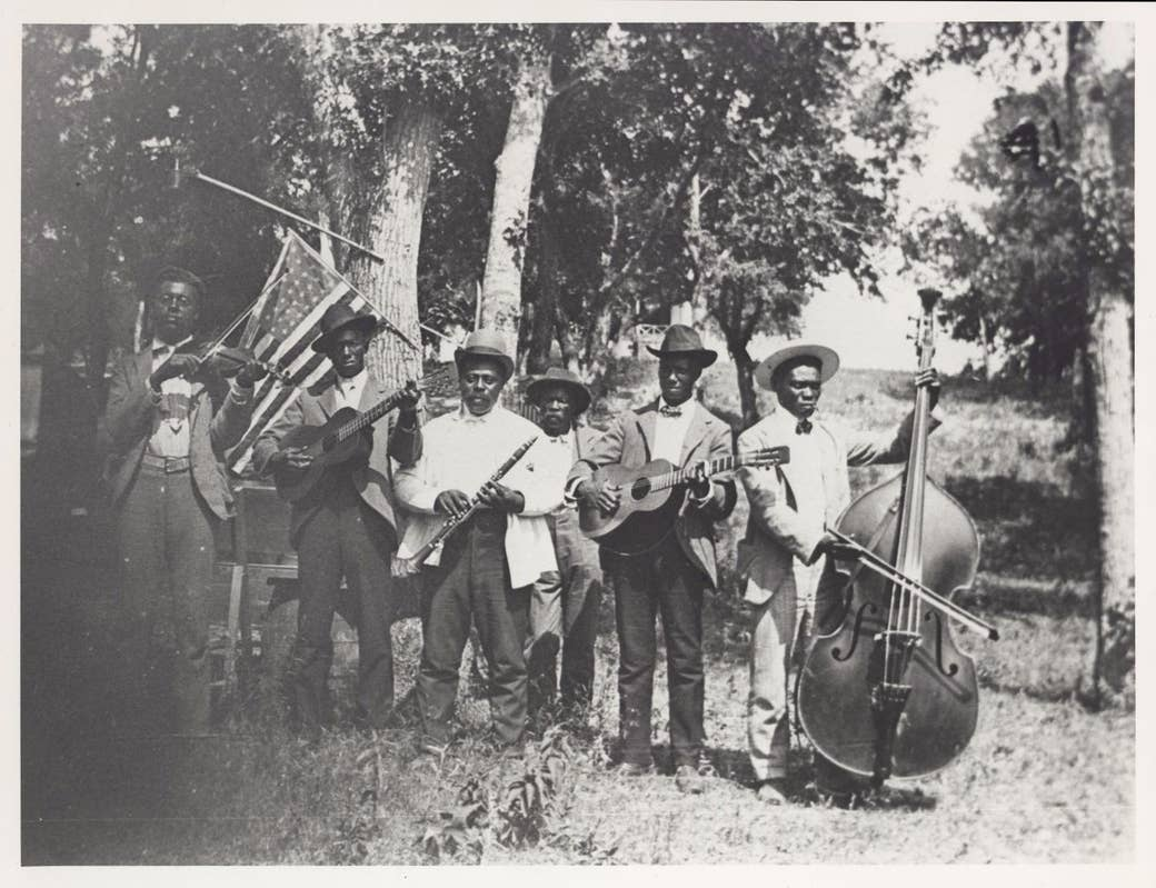 A group of men with musical instruments in a field with an American flag