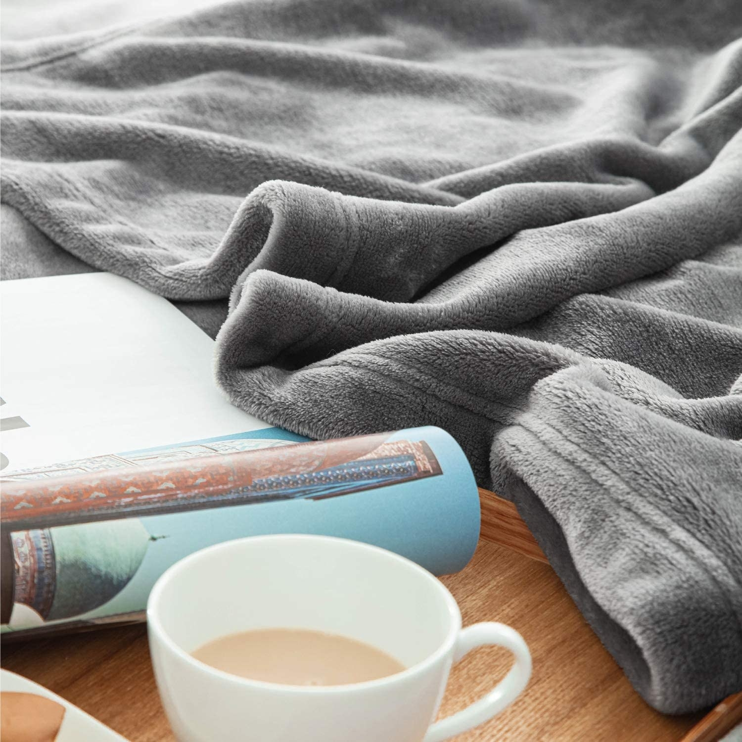 the blanket next to a book and cup