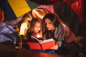 A mother and daughter lay together in a blanket fort reading a book by flashlight.