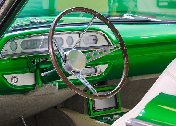 neon vintage car with metal dashboard and thin wheel