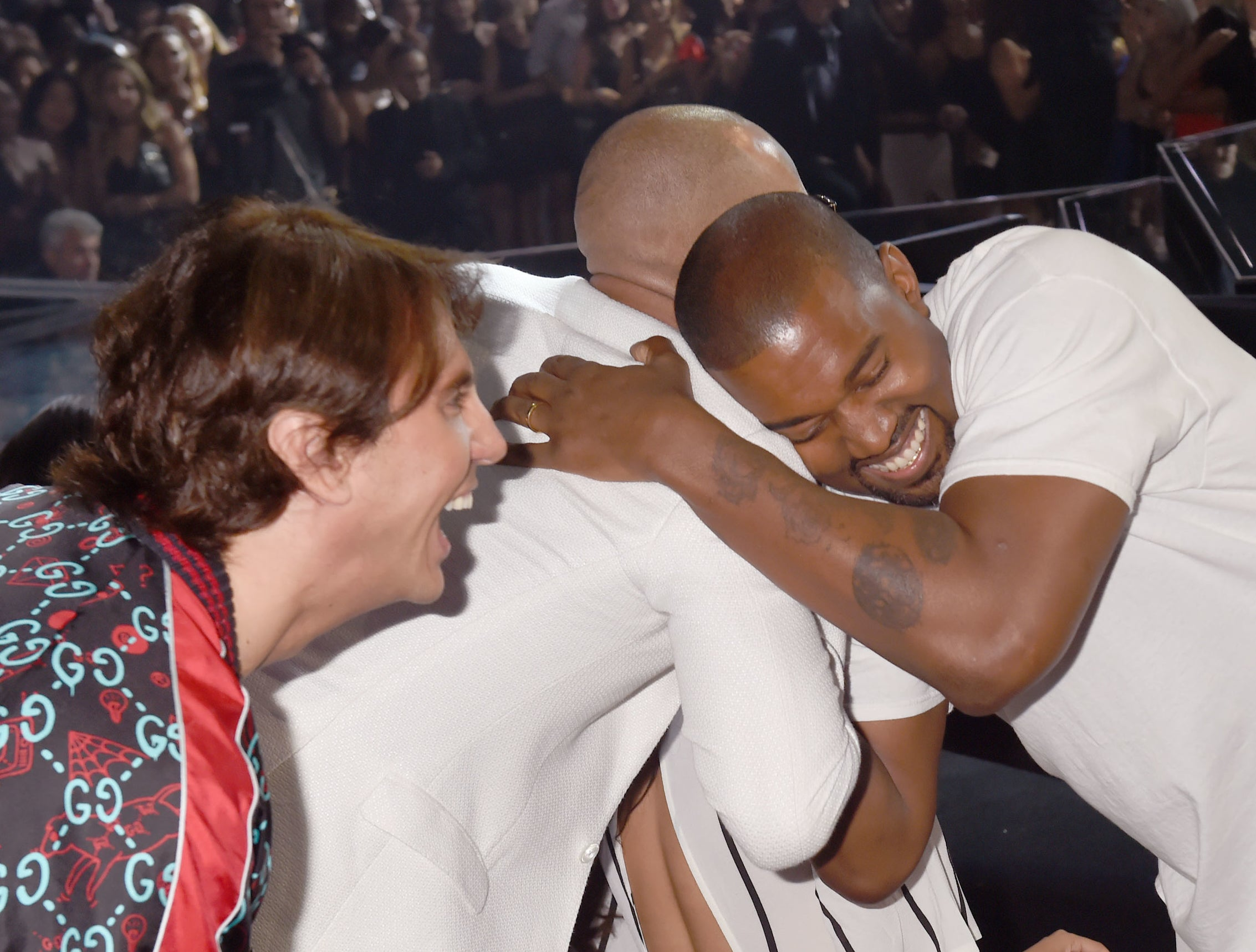 Jonathan leans over and smiles while Kanye hugs another friend