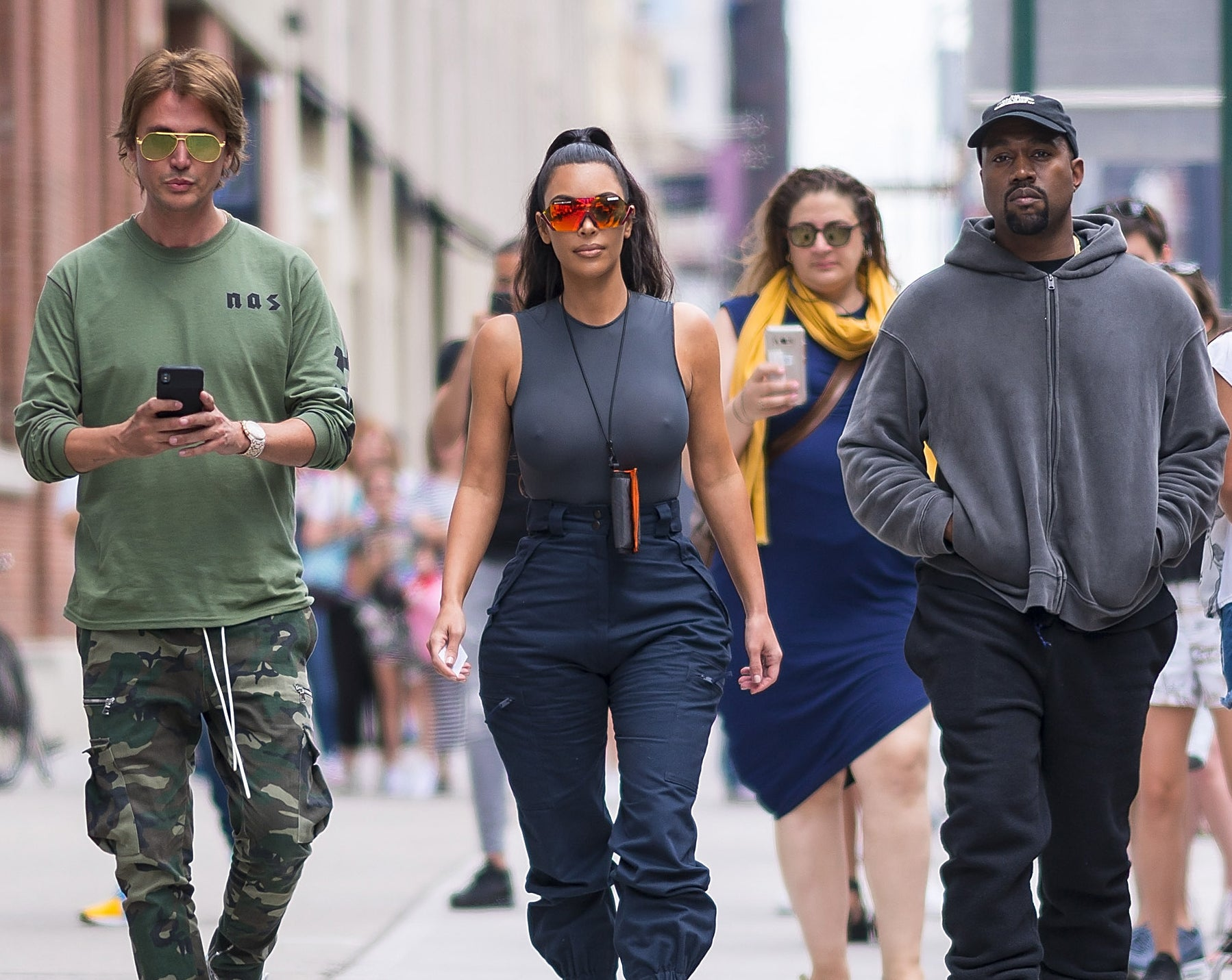 Kim, Jonathan, and Kanye walk together down a street in New York City