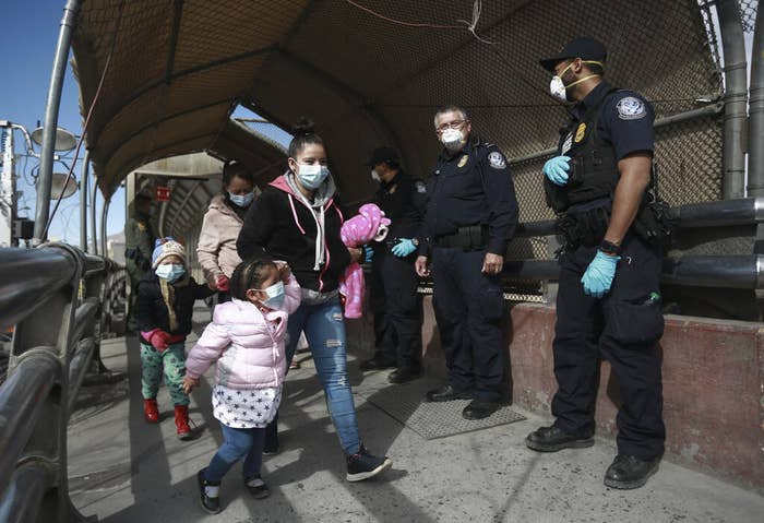 Two young children holding hands with adults walk past border authorities