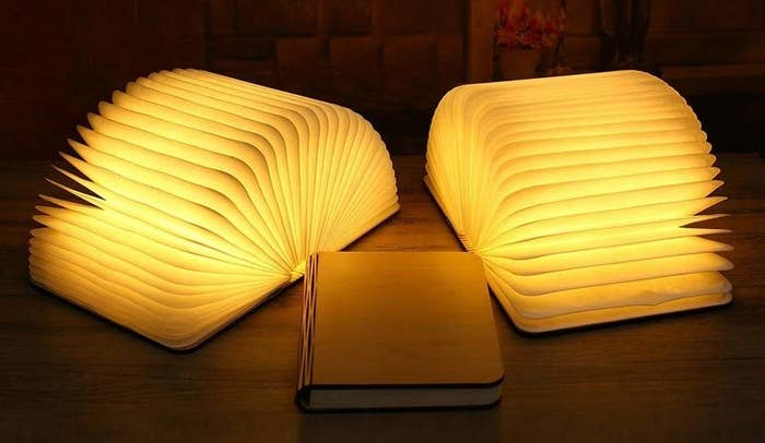 Three folding book lamps, two are open while one is closed.