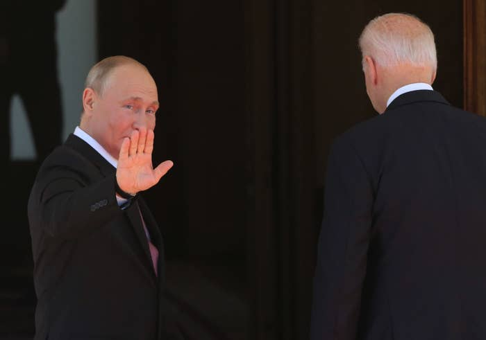 Putin waves to the cameras as Biden's back is turned