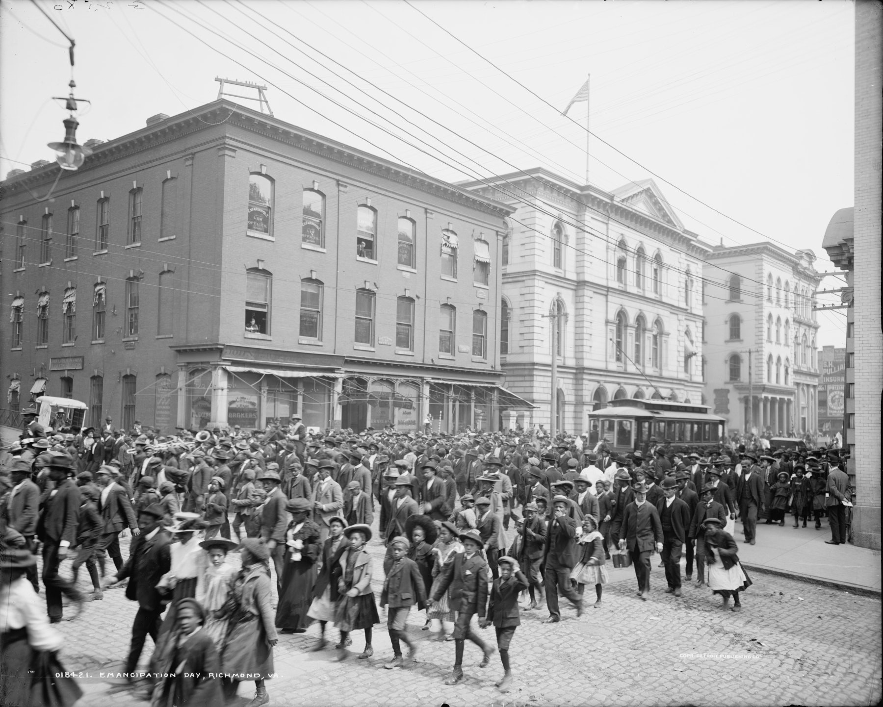 A crowd of people rushes down the street