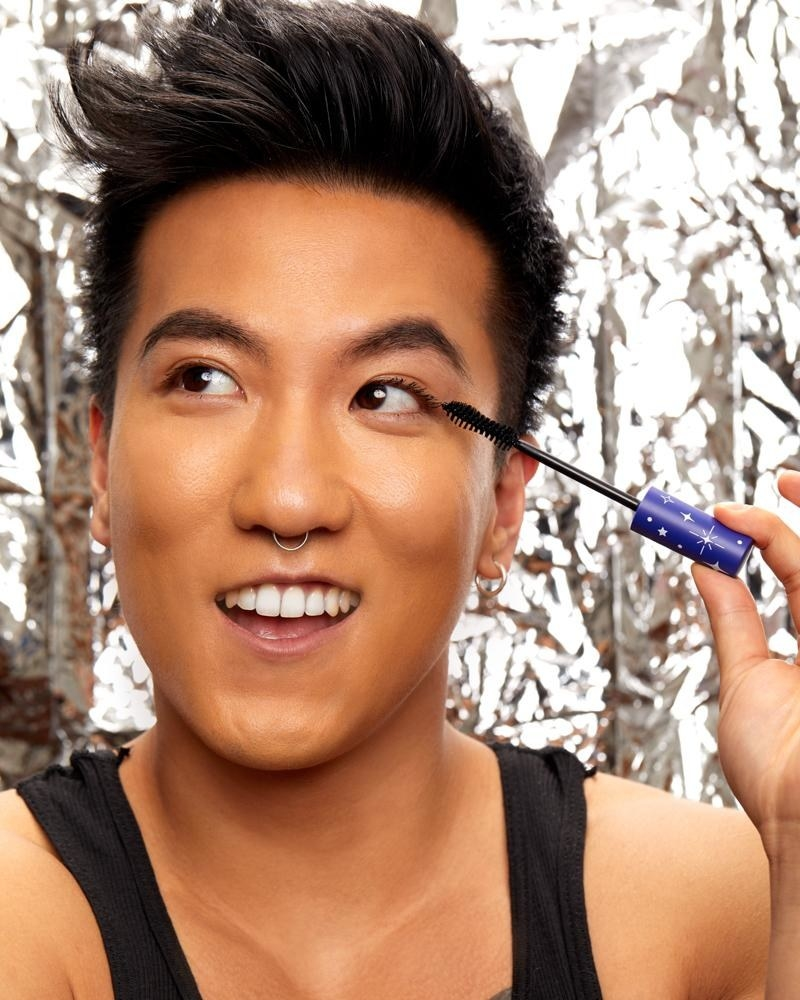 model applying mascara with blue wand handle/cap decorated with white stars and sparkle shapes
