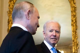 Biden looks at Putin in front of a large gilded mirror